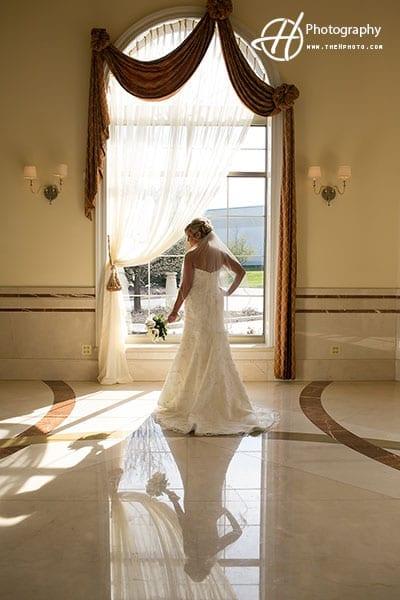 bride posing by the window in ballroom