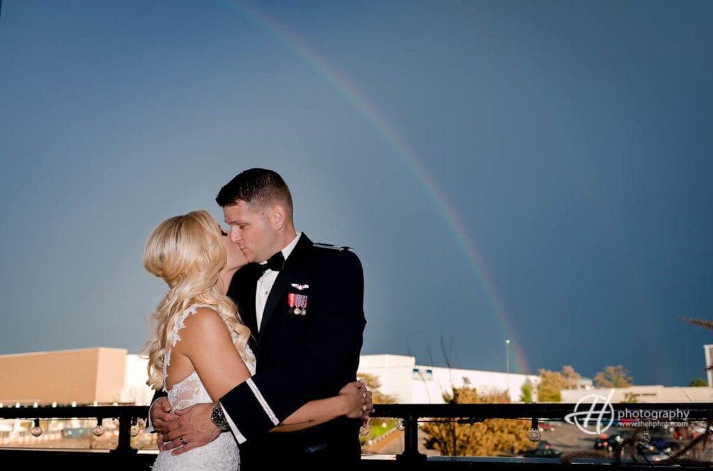 bride and groom kissing under rainbow