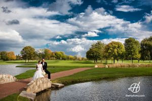 bride and groom posing on a golf course.jpg